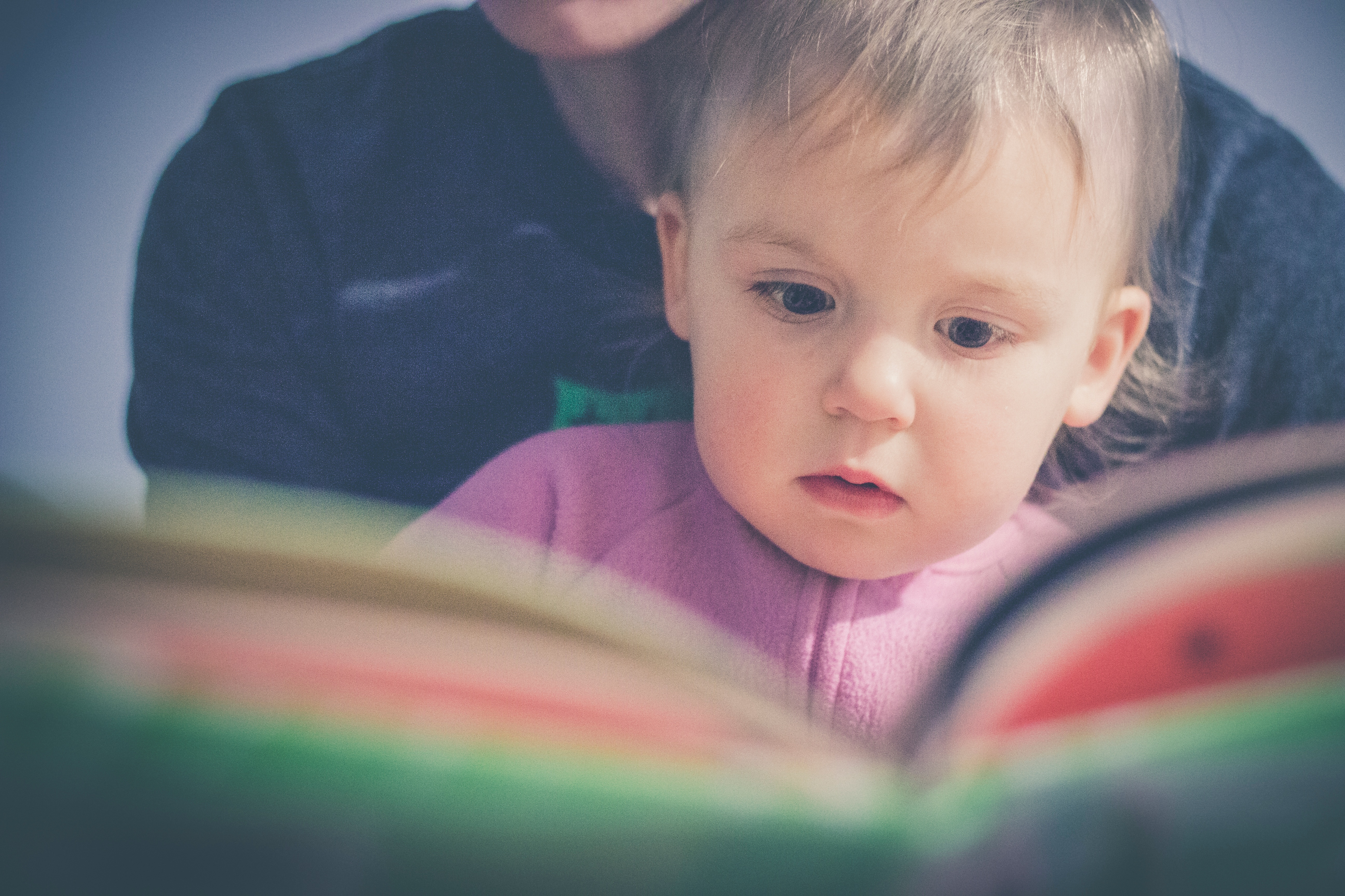 Toddler reading with adult